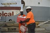 Transport Provider Robert Davis handing over gifts to crew member from Tropic Opal.