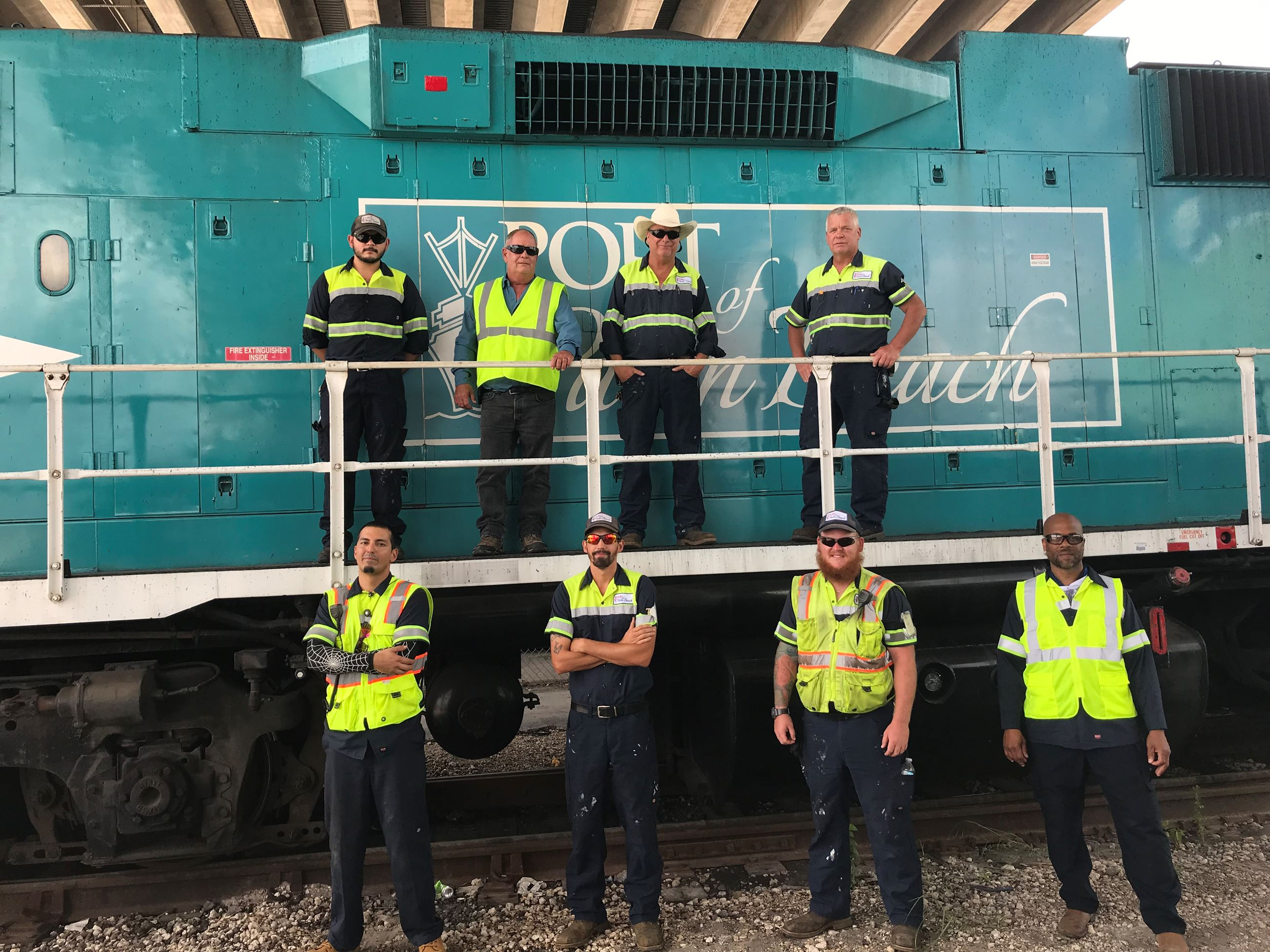 Rail team posing in front of locomotive